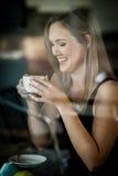 Meisje dat in het venster van een koffiewinkel het drinken koffie wordt gezeten Royalty-vrije Stock Fotografie