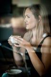Meisje dat in het venster van een koffiewinkel het drinken koffie wordt gezeten Stock Fotografie