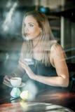 Meisje dat in het venster van een koffiewinkel het drinken koffie wordt gezeten Royalty-vrije Stock Afbeelding