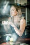 Meisje dat in het venster van een koffiewinkel het drinken koffie wordt gezeten Stock Foto's