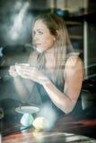 Meisje dat in het venster van een koffiewinkel het drinken koffie wordt gezeten Royalty-vrije Stock Foto