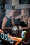 Meisje dat in het venster van een koffiewinkel het drinken koffie wordt gezeten Stock Afbeeldingen