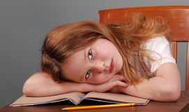 Meisje dat Hoofd op Bureau bepaalt Stock Afbeeldingen