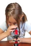 Meisje dat iets met microscoop bestudeert Royalty-vrije Stock Afbeelding
