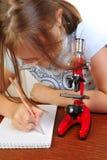 Meisje dat iets met microscoop bestudeert Stock Foto