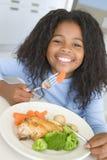 Meisje dat kip en plantaardig diner thuis eet Stock Foto
