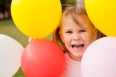 Meisje dat kleurrijke ballons houdt stock foto's