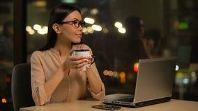 Meisje dat koffie heeft terwijl het werken aan laptop, draadloos Internet in cafetaria stock footage
