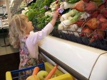 Meisje dat in kruidenierswinkelopslag winkelt Stock Fotografie