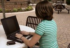 Meisje dat laptop buiten met behulp van royalty-vrije stock afbeelding