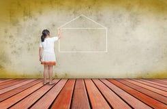 Meisje dat lijn van huis op concrete muur uitschrijft Royalty-vrije Stock Fotografie