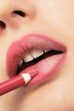 Meisje dat lippenvoering toepast stock foto
