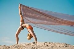 Meisje dat met grote oranje doek danst Stock Afbeeldingen