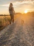 Meisje dat met haar hond loopt stock fotografie