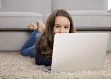 Meisje dat met laptop werkt Stock Foto's