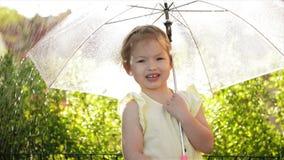 Meisje dat met paraplu in park op de weg glimlacht Langzame Motie stock videobeelden