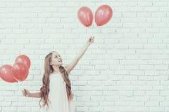 Meisje dat met Rode Baloons zich in Witte Zaal bevindt stock foto's