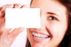 Meisje dat met steunen adreskaartje voorstelt stock afbeelding