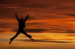 Meisje dat met vreugde bij zonsondergang springt Royalty-vrije Stock Foto
