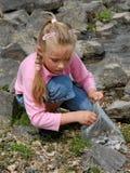 Meisje dat mosselen verzamelt Stock Foto's