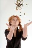 Meisje dat muntstukken werpt in lucht stock foto's