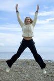 Meisje dat naast Oostzee springt stock afbeeldingen