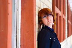 Meisje dat omhoog dichtbij een Bakstenen muur kijkt Stock Fotografie