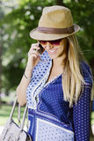 Meisje dat op de telefoon met een hoed glimlacht Stock Afbeeldingen