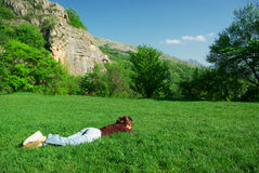 Meisje dat op de weide rust Stock Afbeeldingen