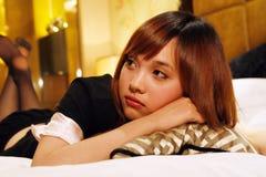 Meisje dat op een bed ligt stock foto