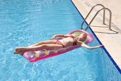 Meisje dat op een matras zonnebaadt Stock Afbeeldingen
