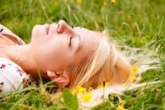 Meisje dat op groen gras ligt stock afbeelding