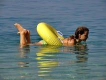 Meisje dat op het stuk speelgoed in het overzees ligt stock foto