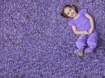 Meisje dat op purpere bloemen ligt royalty-vrije stock foto