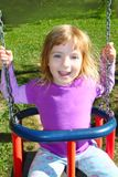 Meisje dat op schommeling gelukkig in het park van het weidegras slingert Royalty-vrije Stock Foto