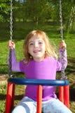 Meisje dat op schommeling gelukkig in het park van het weidegras slingert Royalty-vrije Stock Afbeeldingen