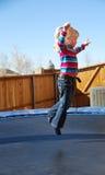 Meisje dat op trampoline springt Stock Afbeeldingen