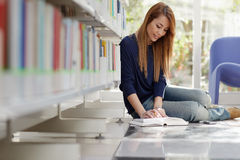 Meisje dat op vloer in bibliotheek bestudeert Stock Foto