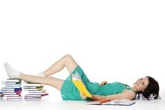 Meisje dat op vloer met boeken het lezen ligt. Stock Fotografie