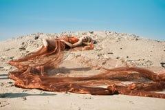 Meisje dat op zand in oranje doek ligt Stock Foto's
