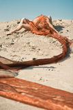 Meisje dat op zand in oranje doek ligt Stock Foto