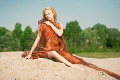 Meisje dat op zand in oranje doek ligt Royalty-vrije Stock Afbeelding