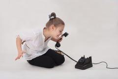 Meisje dat oude telefoon bekijkt stock foto