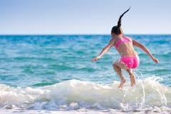 Meisje dat over overzeese golf springt. De zomer, vakantie Stock Afbeelding