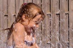 Meisje dat pret met water heeft stock afbeeldingen