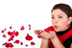 Meisje dat rode bloemblaadjes blaast Stock Fotografie