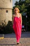 Meisje dat in rode kleding een stadsstraat kruist Royalty-vrije Stock Afbeeldingen