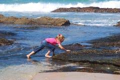Meisje dat rotsen op strand beklimt Stock Fotografie