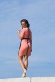 Meisje dat in roze kleding tegen de hemel loopt royalty-vrije stock afbeeldingen