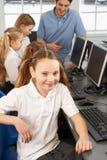 Meisje dat in schoolklasse aan camera glimlacht stock foto